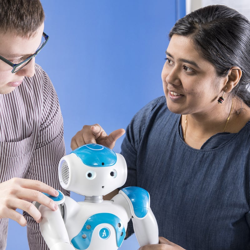 Student and faculty in a discussion with a robot