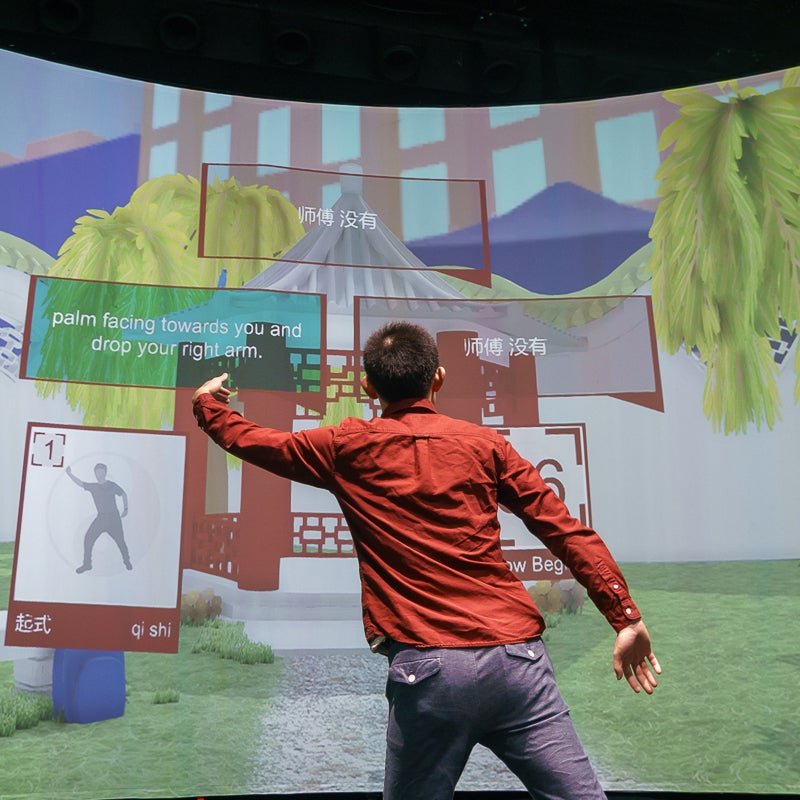 Student interacting with a VR program on a large screen