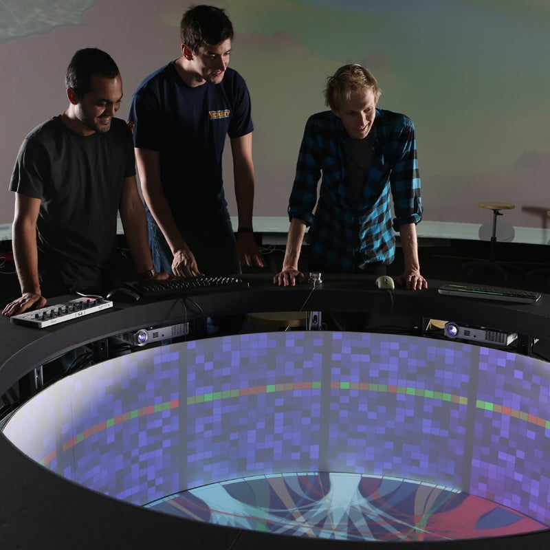 Three people looking down on a 360 degree monitor
