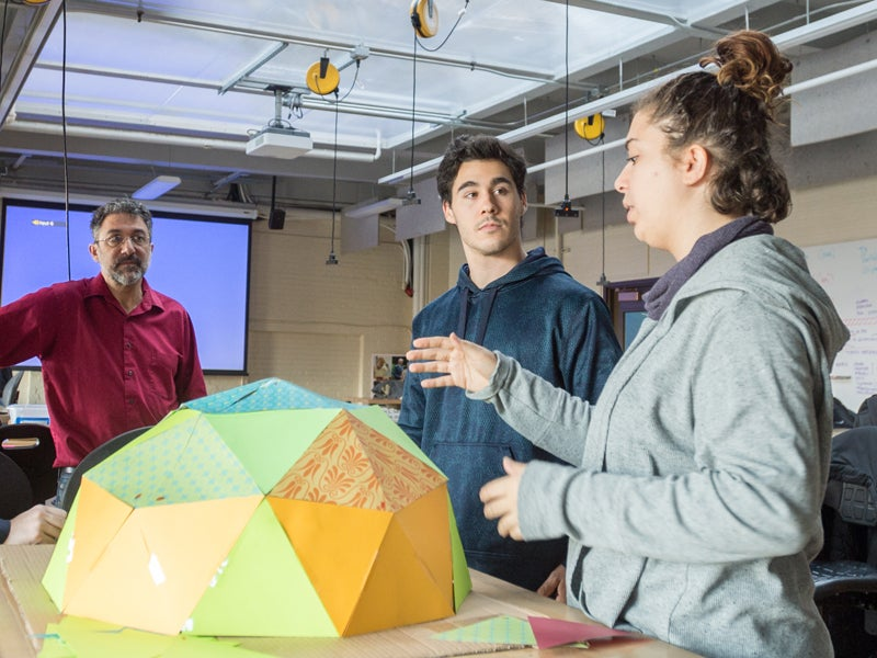 Students discussing geodesic dome structure with professor
