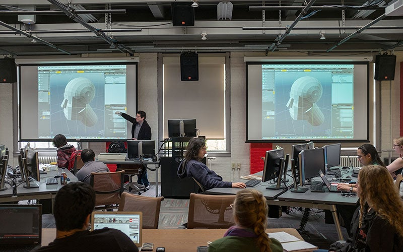 Professor Ben Chang teaching in front of two large screens